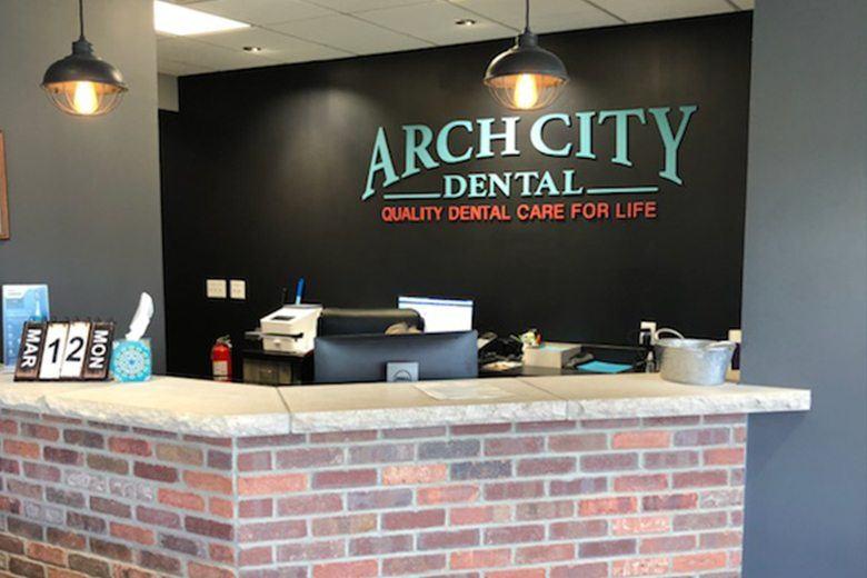 Arch City Dental logo on wall