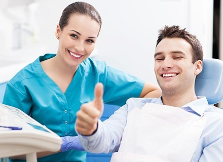 Smiling dental assistant next to patient in dental chair giving thumbs up