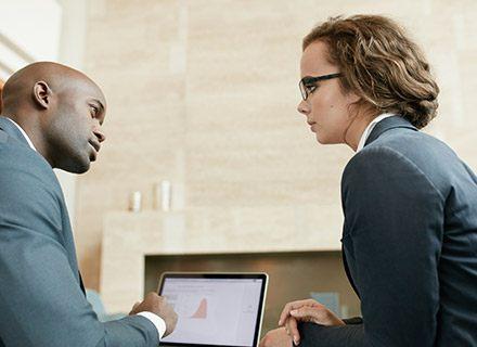 Man and woman talking at computer