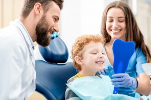 boy with dentist and dental assistant