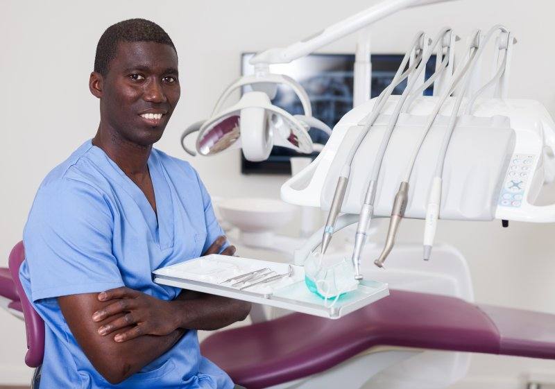 a male dental assistant smiling while seated in a treatment room