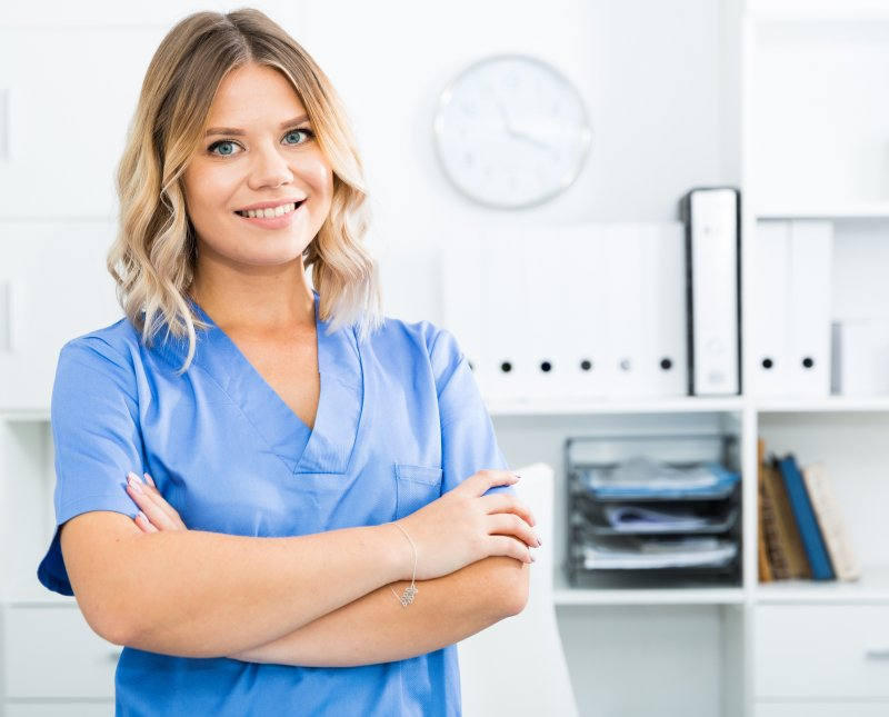 a female dental assistant wearing scrubs and standing with her arms crossed