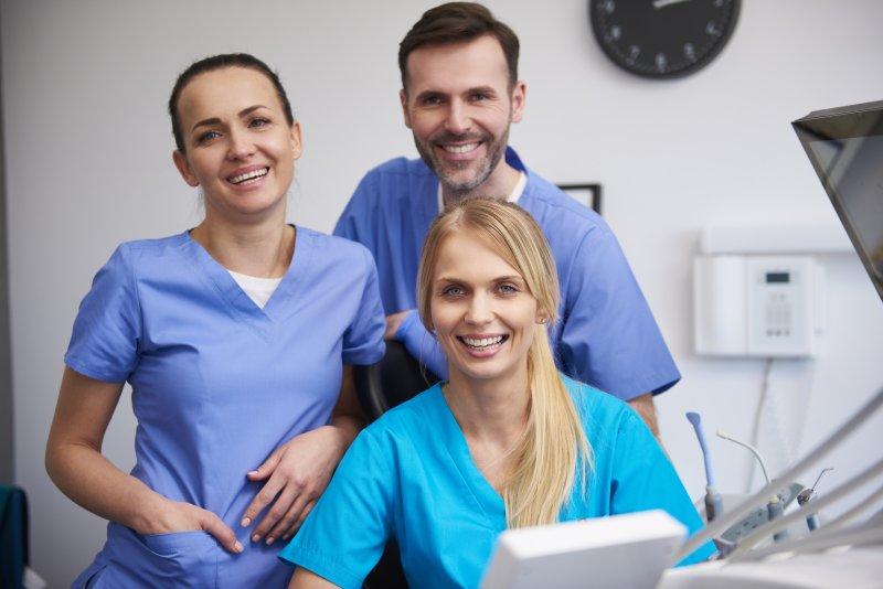 two women and one man serving as dental assistants in a dentist's office