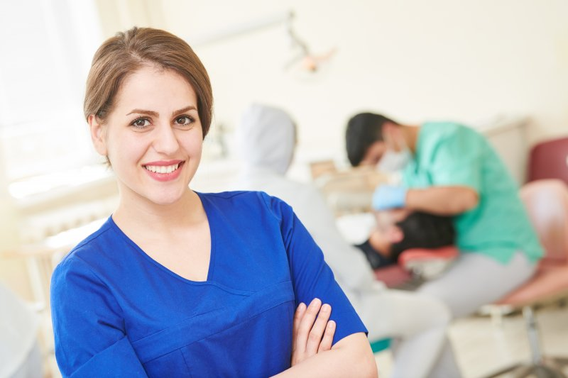 a young, female dental assistant smiles while a dentist examines a male patient in the background