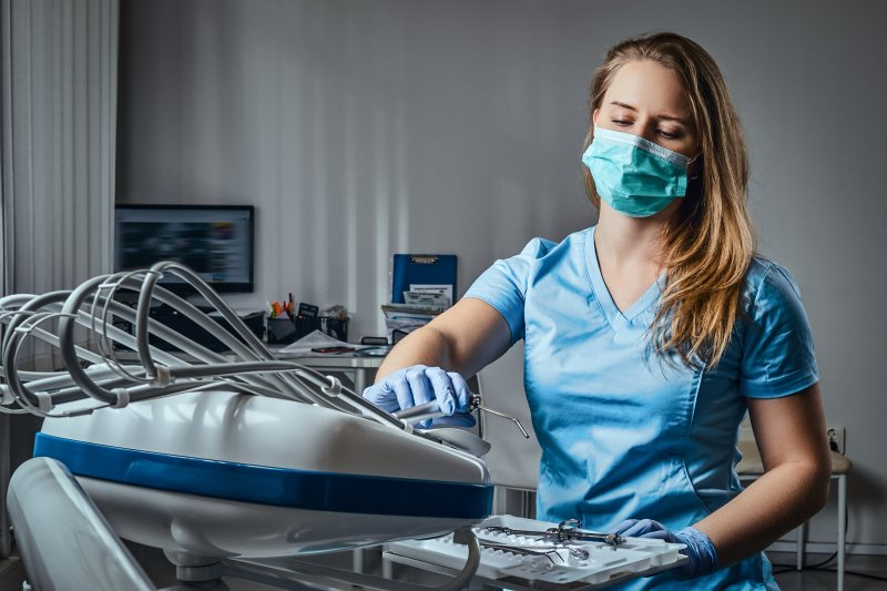 a female dental assistant preparing a treatment room by placing the correct dental instruments