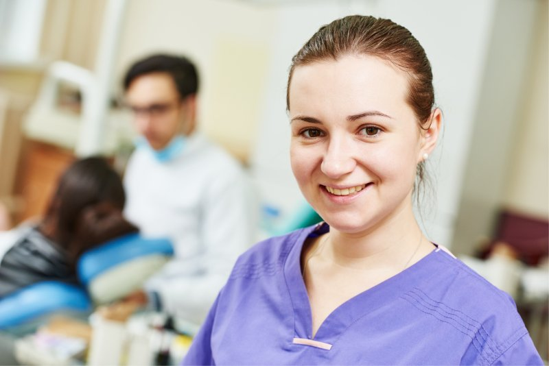 a female dental assistant smiling while a dentist examines a patient