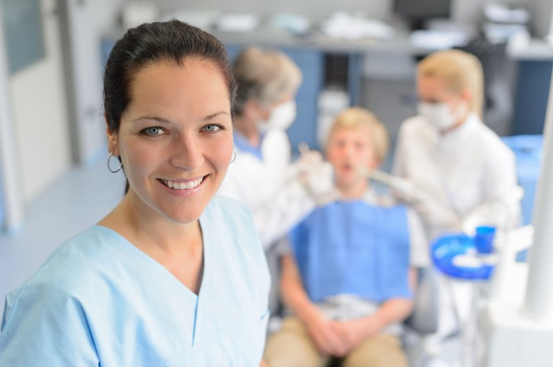 a female dental assistant smiles while the dentist and dental hygienist provide services to a patient