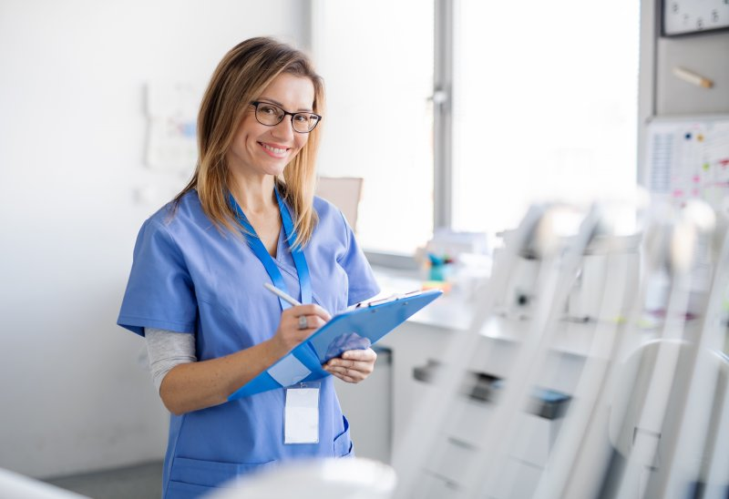 a young dental assistant charting while at work